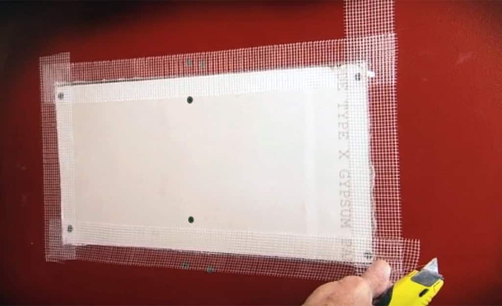 A person sealing drywall patch seams with drywall joint tape.