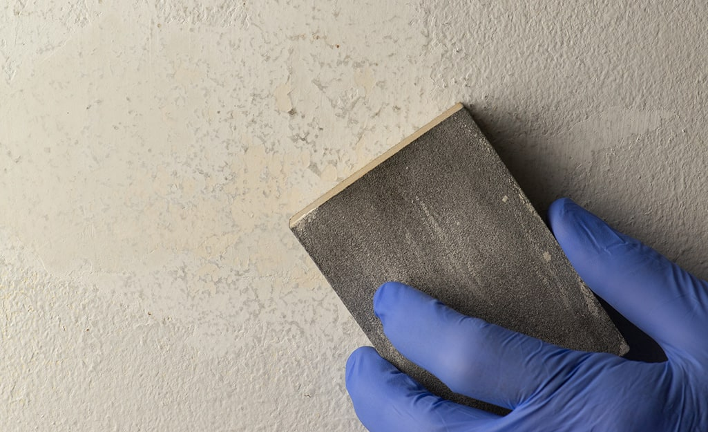 Someone sanding a wall repair.