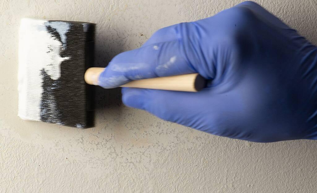 Someone priming a wall repair.