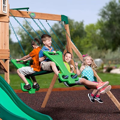 Children are enjoying playing on a swing set.
