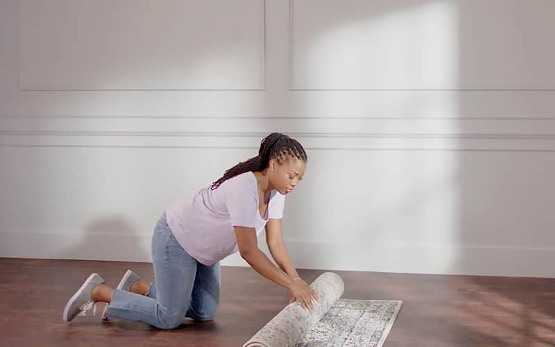 Woman removing rugs in preparation for painting.
