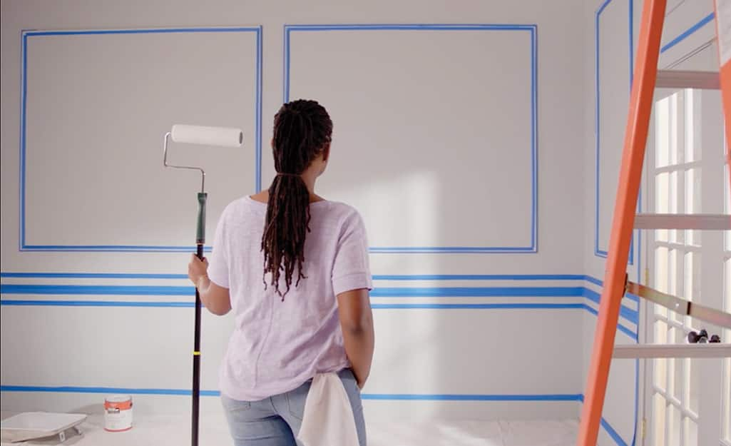 A woman holding a paint roller is ready to paint her prepped walls.