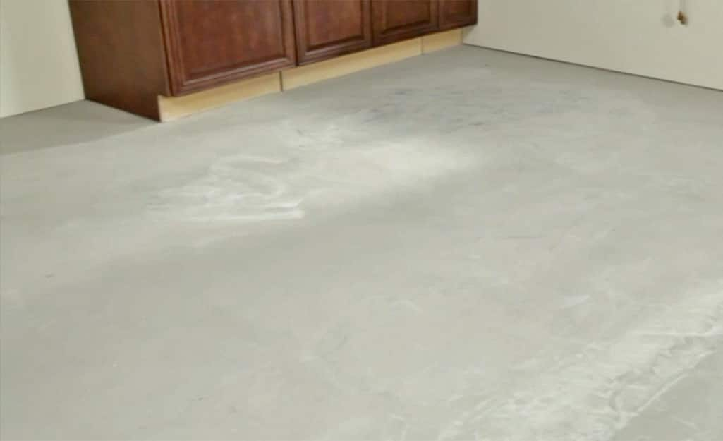Cabinets placed on the concrete subfloor of a room.
