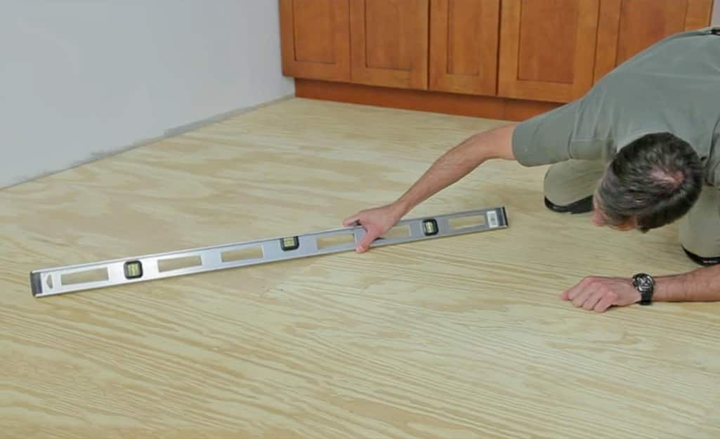 A person using a level to locate low spots on a wood subfloor.