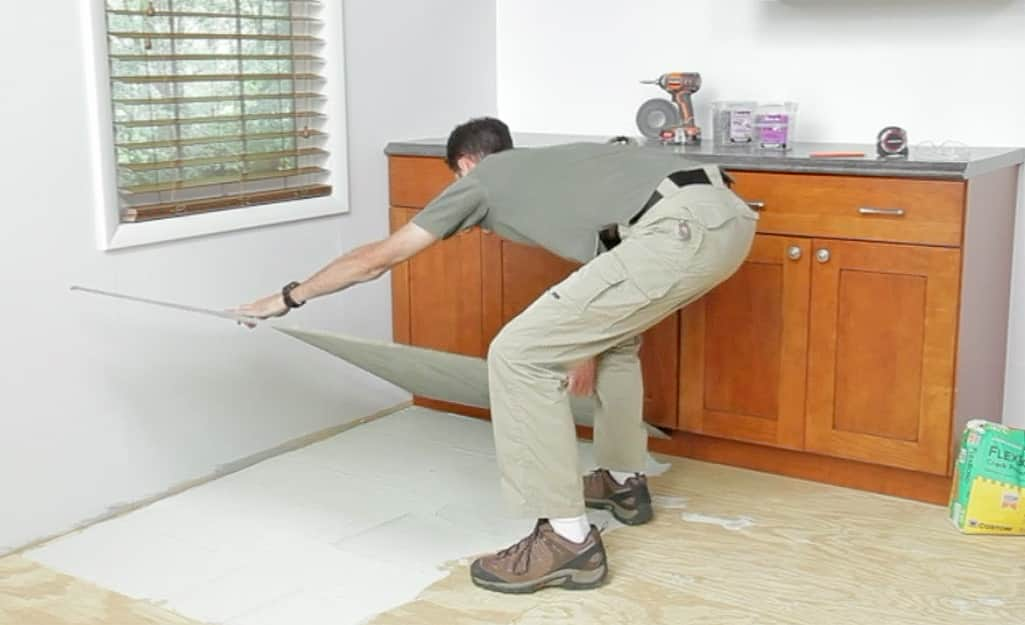 A person placing a sheet of backerboard on a wood subfloor.