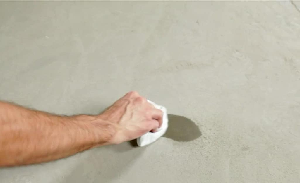 A person wiping water from a concrete subfloor.