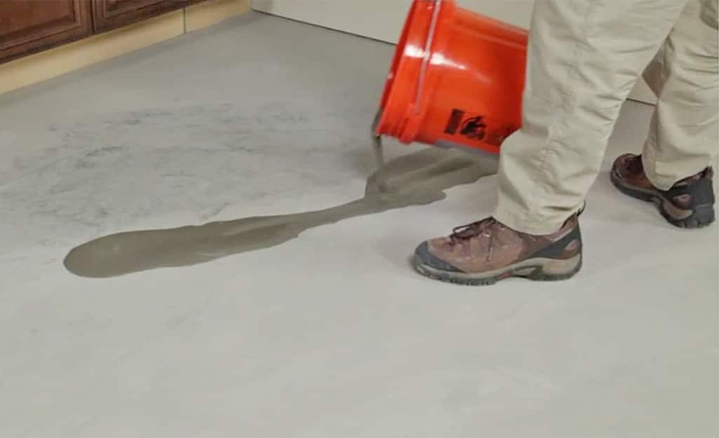 A person pouring leveling compound on a concrete subfloor.