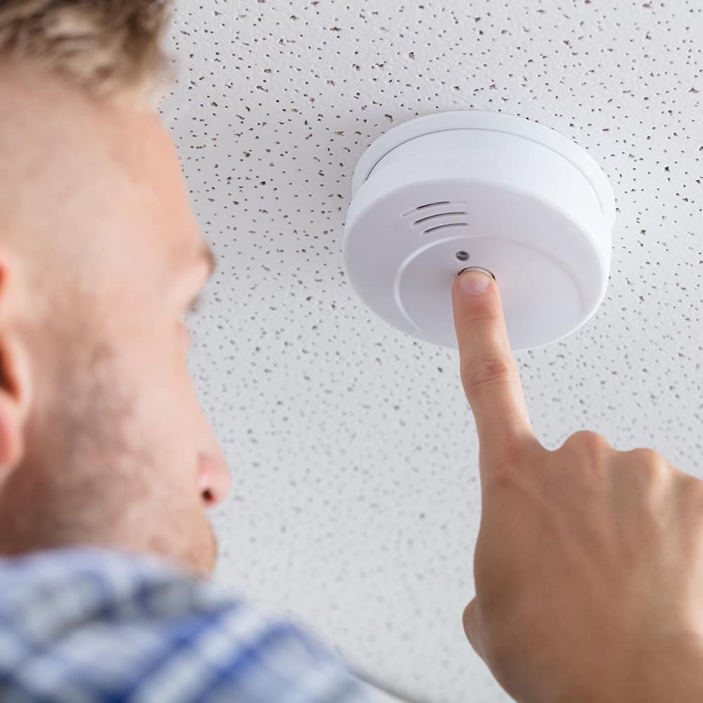 A person tests a smoke alarm on the ceiling.