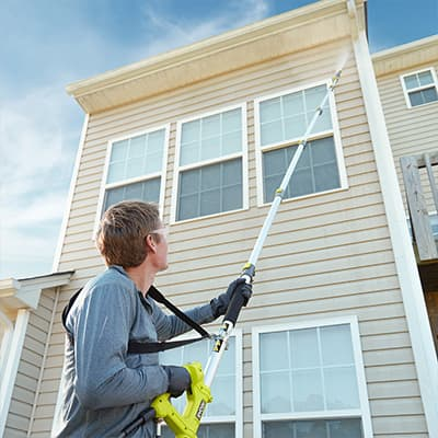 A man pressure washes a two-story home.