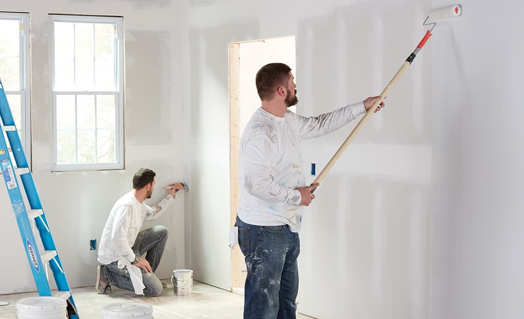 Two people applying a coat of primer to an unfinished wall.