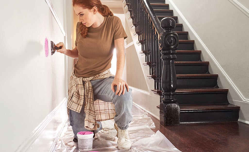 A person using a scraper to prepare a wall for a coat of primer.