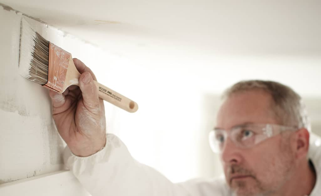 A person using a paint brush to apply primer on a wall at the edge of the ceiling.