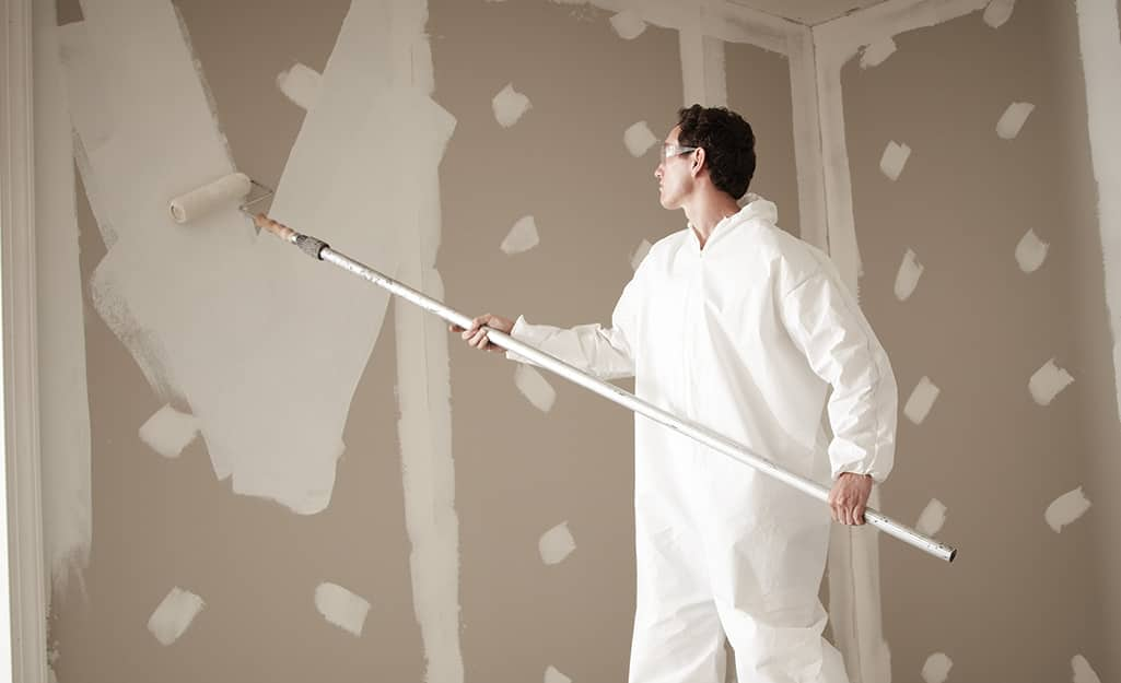 A person using a paint roller on an extension pole to apply primer to an unfinished wall.