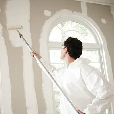 A person using a roller to apply primer to a wall.