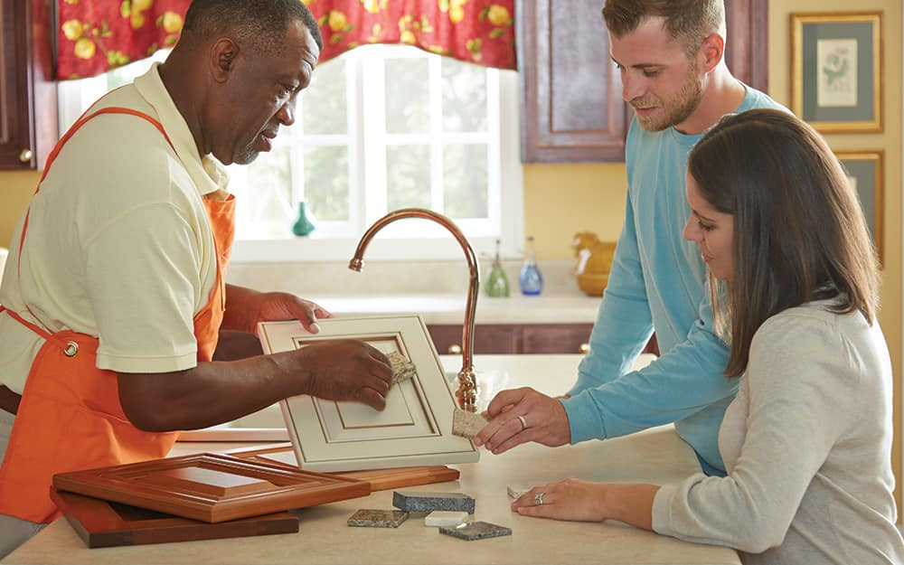 Three people discuss a kitchen cabinet refacing project.
