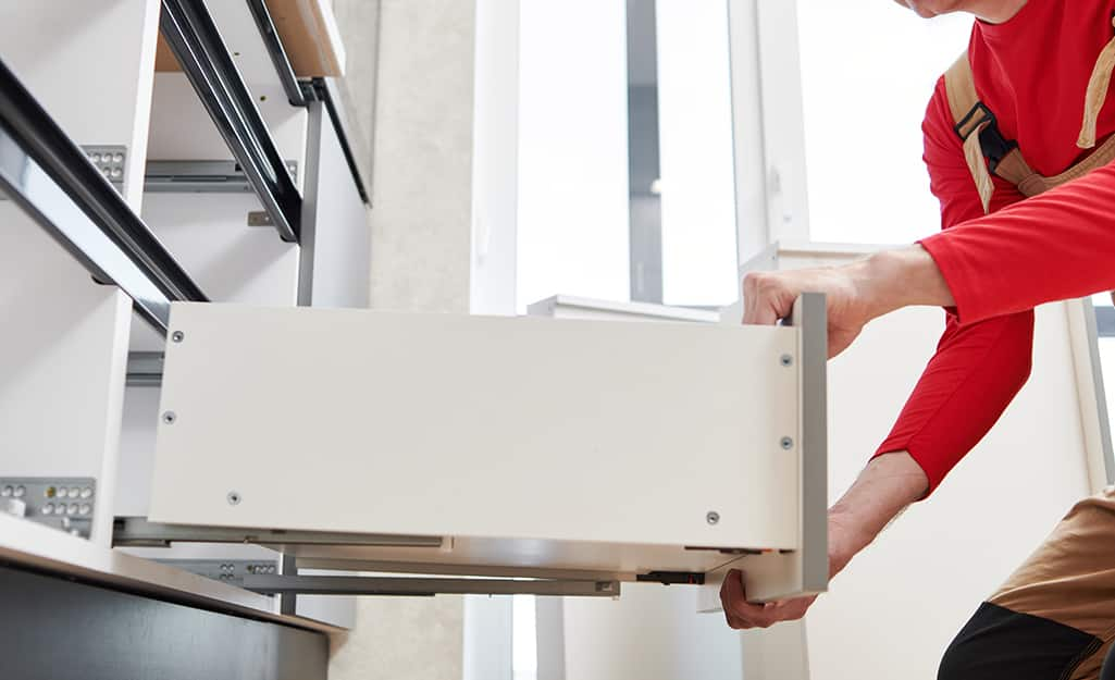 A person removes a kitchen cabinet drawer.