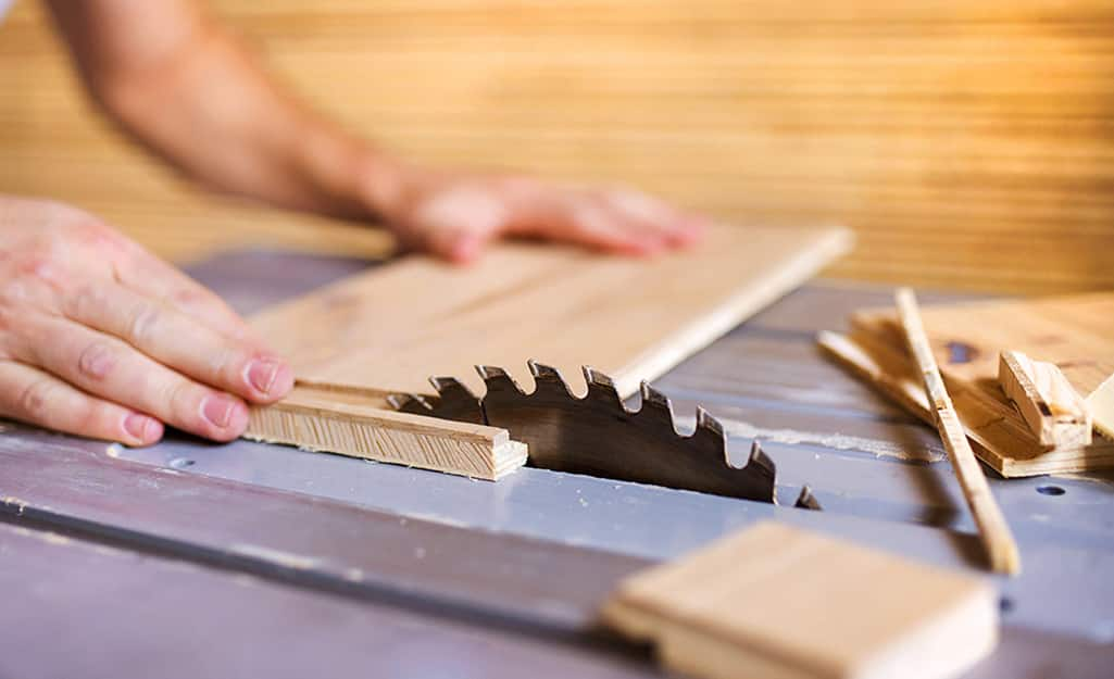 A person cuts plywood for a kitchen cabinet refacing.