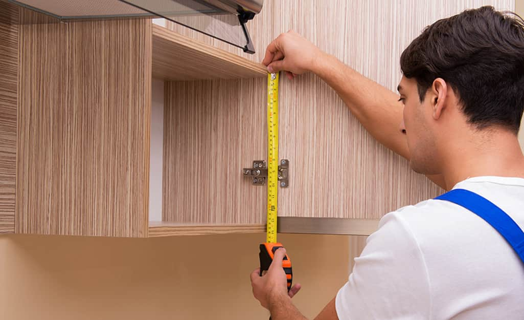 A person measures the stiles of a cabinet to be refaced.