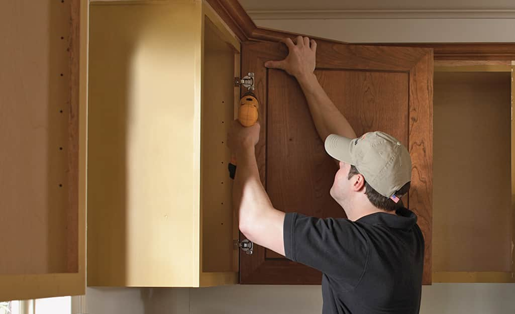 A person reattaches a door to a kitchen cabinet.