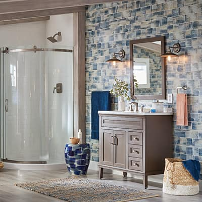 A bathroom features a vanity in front of a wall with tile and a shower with a glass door.