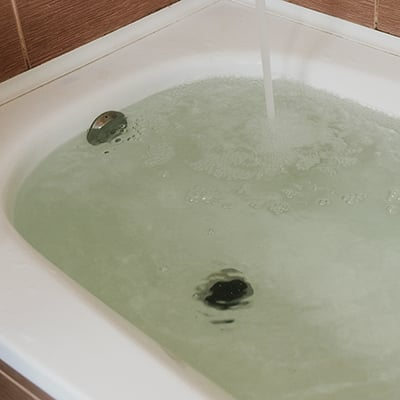 A bathtub filling with water.