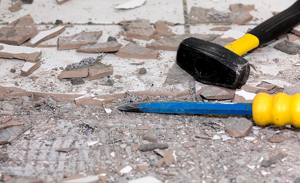 A peen hammer and chisel lying on broken tile.