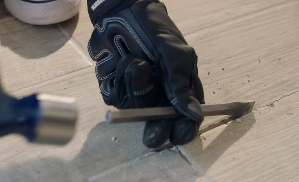Someone removing tile grout with a chisel.