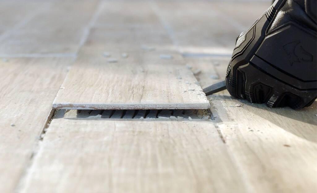 Someone prying up old ceramic flooring.