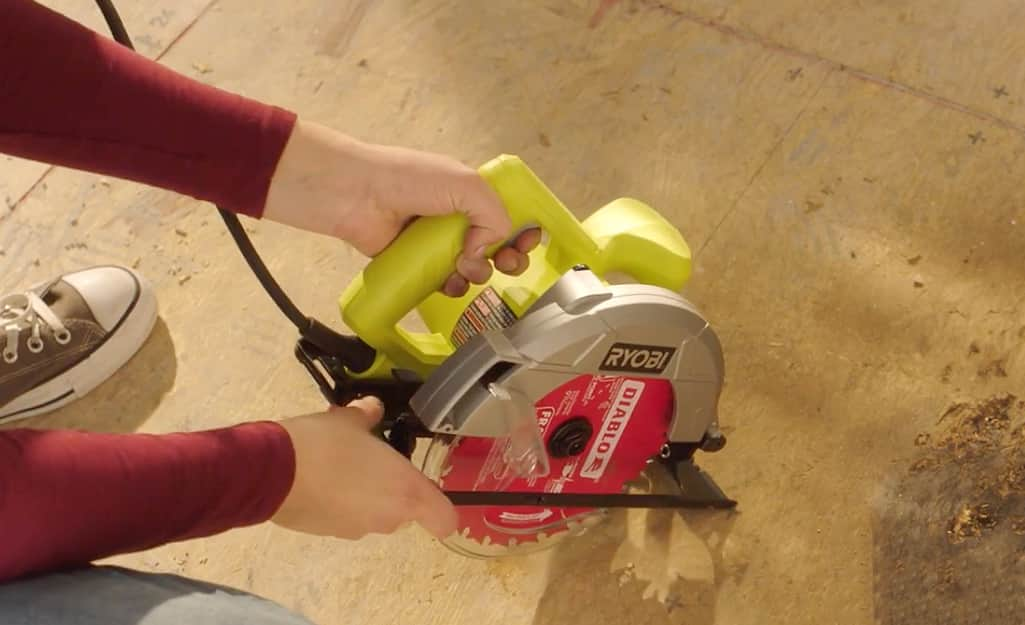 Someone using a circular saw on a wood subfloor.