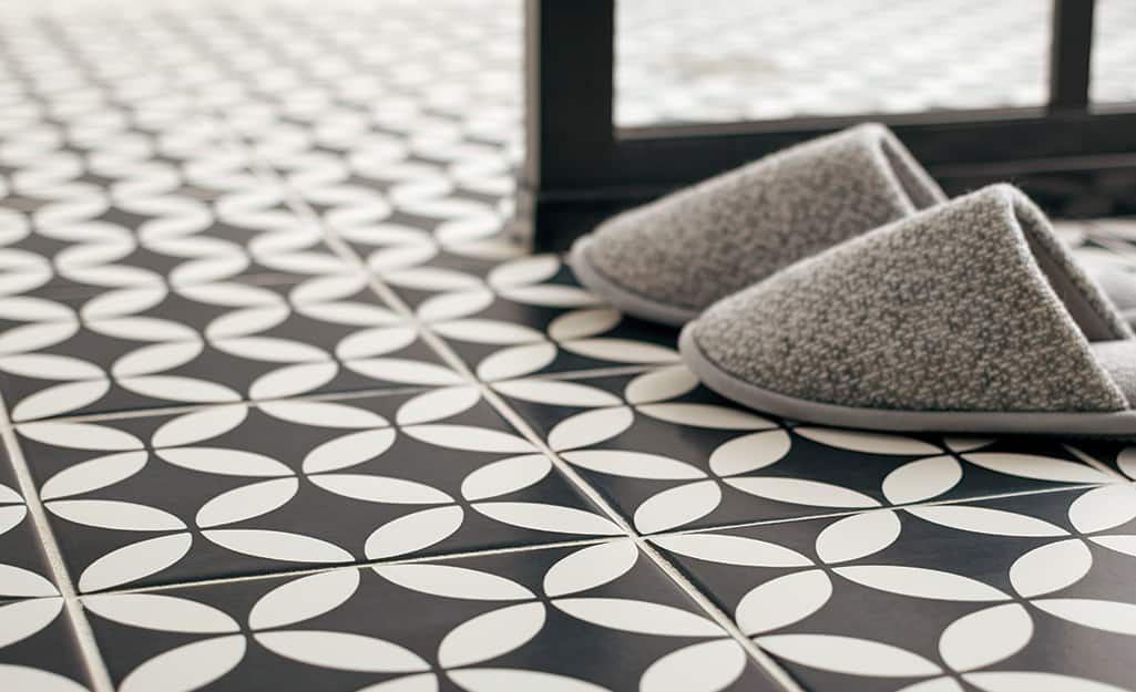 Slippers placed on black and gray bath tile floor.
