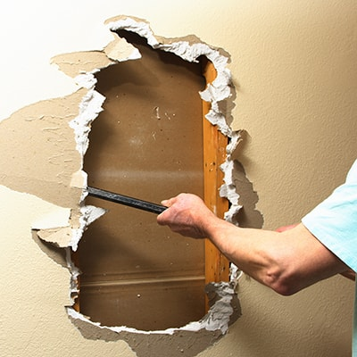 A person uses a pry bar to remove drywall.