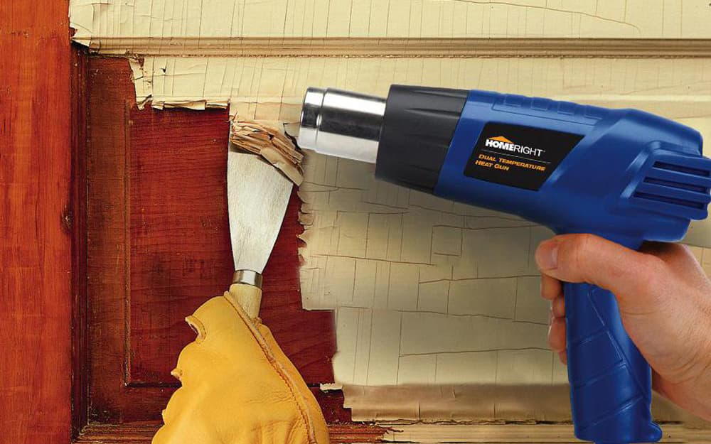 Person using a heat gun and putty knife to remove paint.