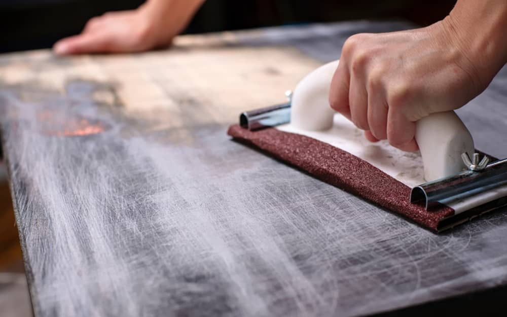A person using a manual hand sander and sandpaper to remove paint from wood.