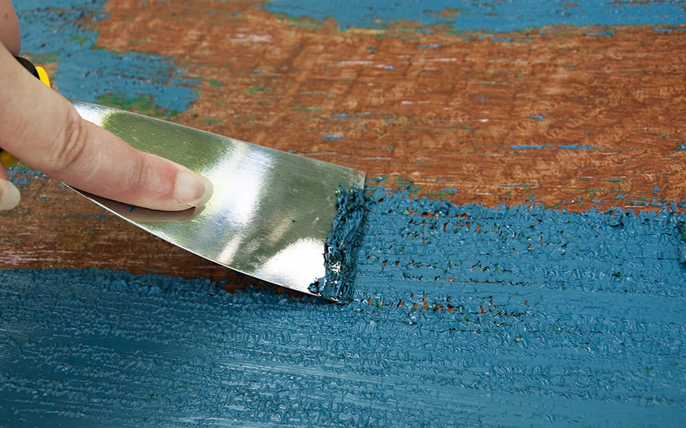 Person using a scraper to remove paint from wood.