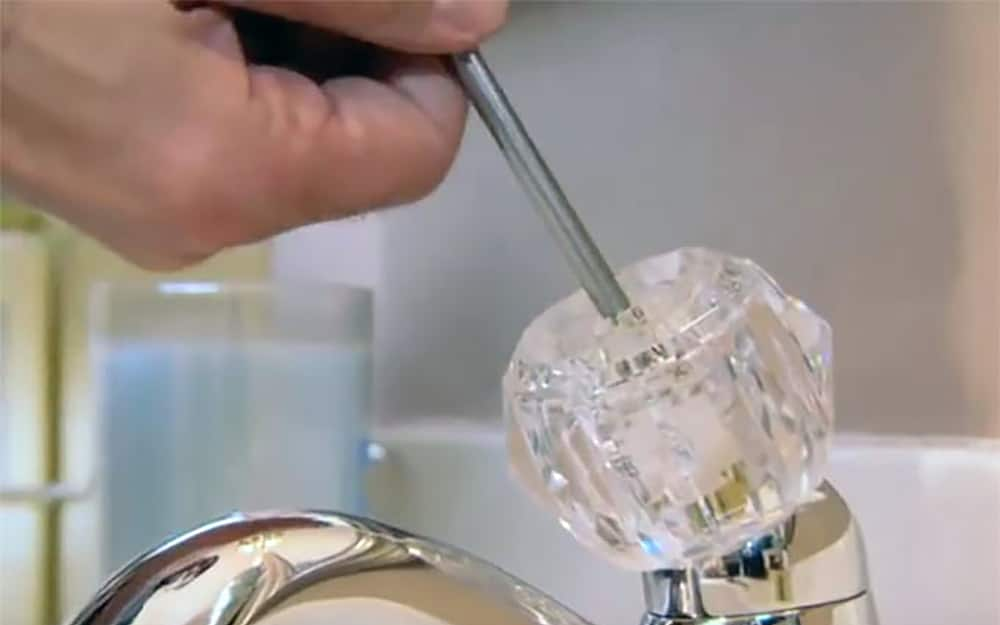 A screw is loosened to remove the handle from a ball faucet.