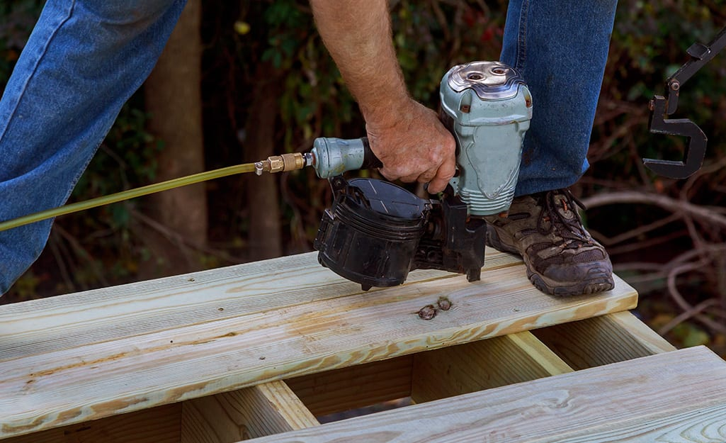 Person attaching new decking with a nailer.