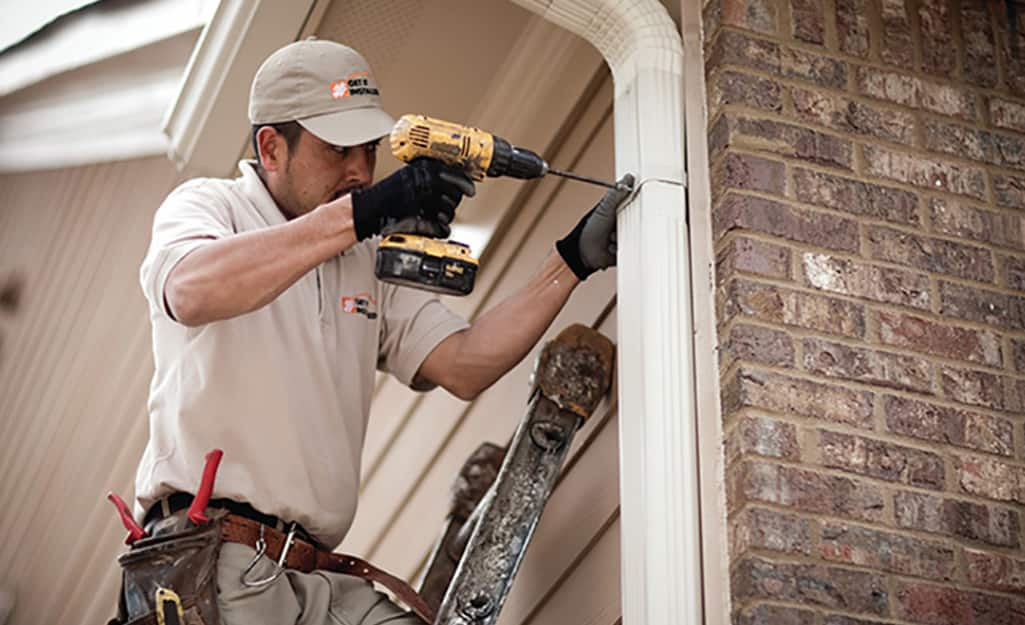 A person using a drill to reattach a downspout to the side of a house.