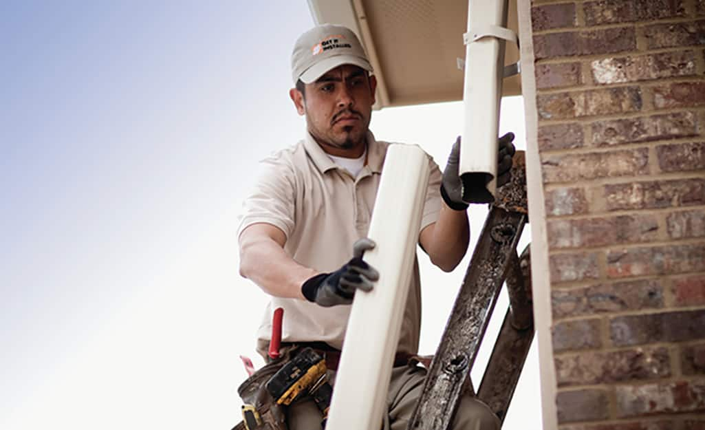 A man inspecting a removed section of downspout.