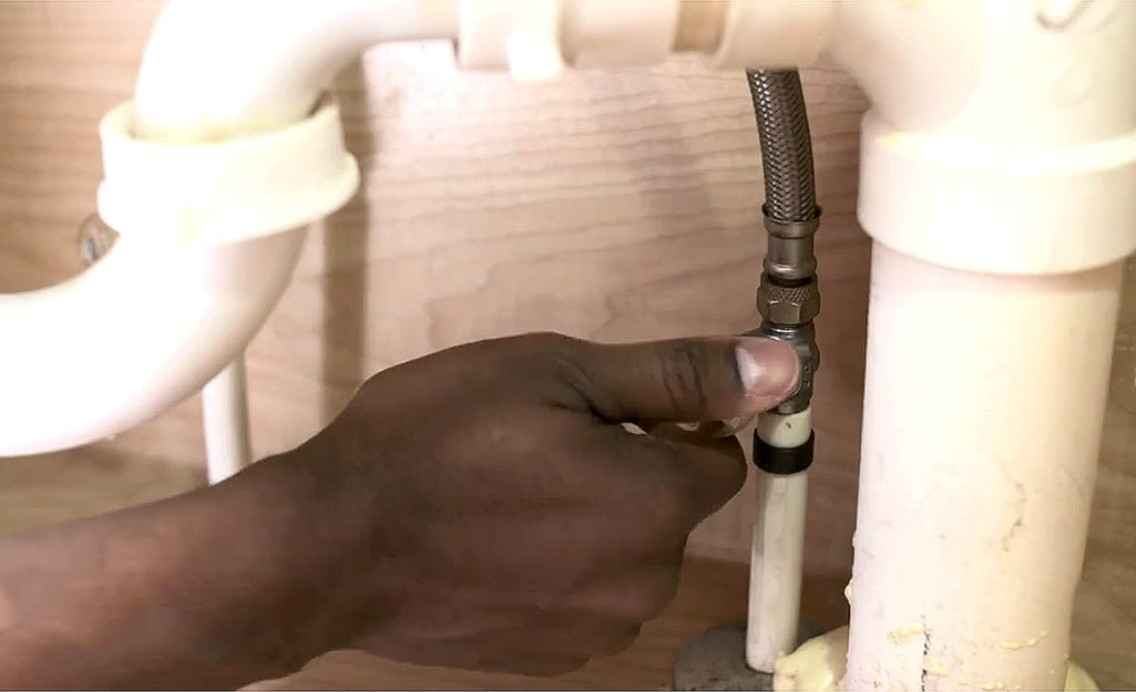 A person shuts off the water before replacing a bathroom faucet.