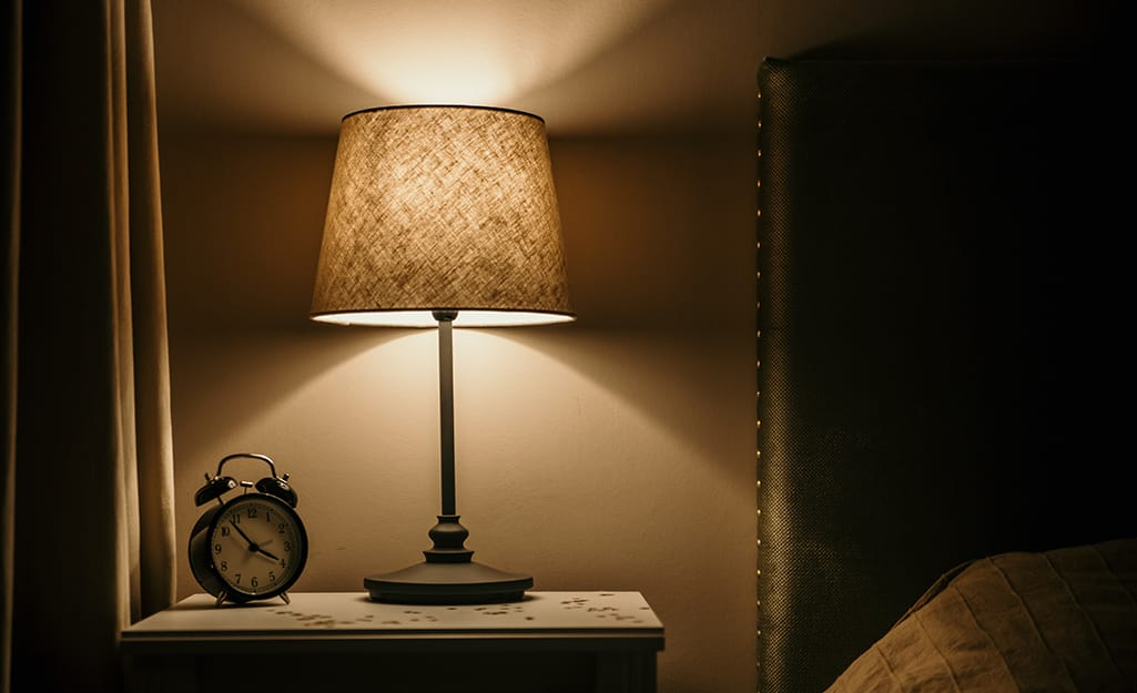 A rewired lamp on a bedside table illuminates a vintage alarm clock and bed.