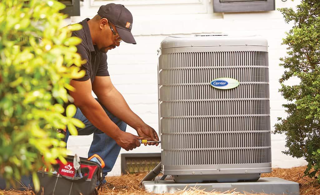 A Home Depot associate repairing an air conditioning unit.