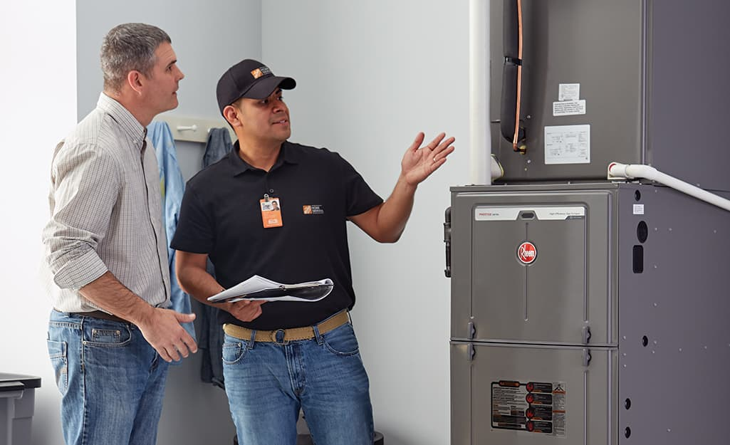 A Home Depot associate standing next a homeowner and gesturing to a furnace.