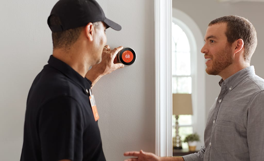 A Home Depot associate standing next to a homeowner and adjusting a smart thermostat on a wall.
