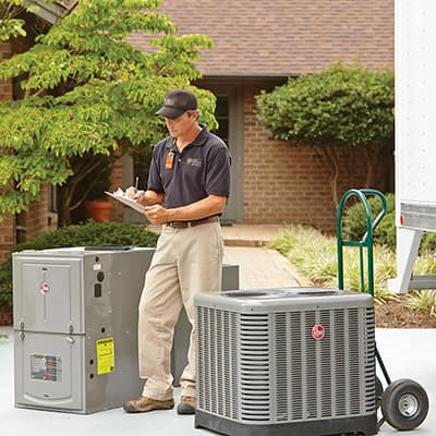 A Home Depot associate standing next to a new air conditioner and heater outside a home.