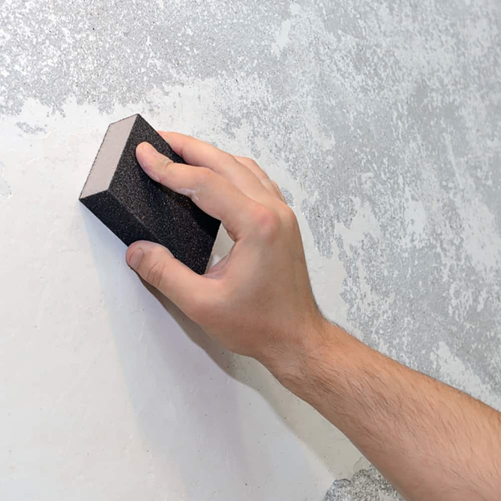 person sanding drywall with a sponge