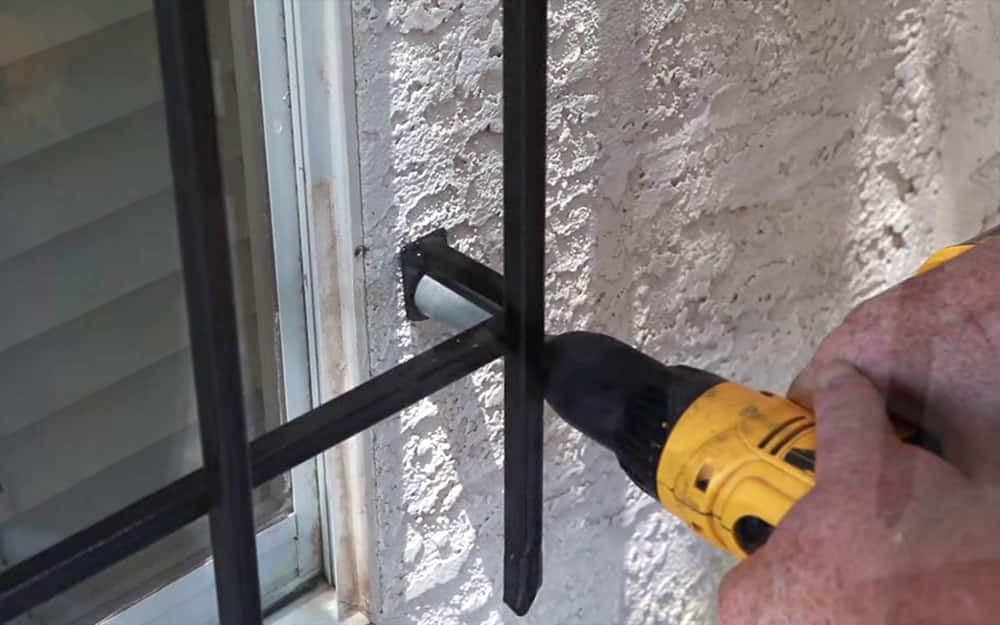 person installing exterior window security bars with a drill