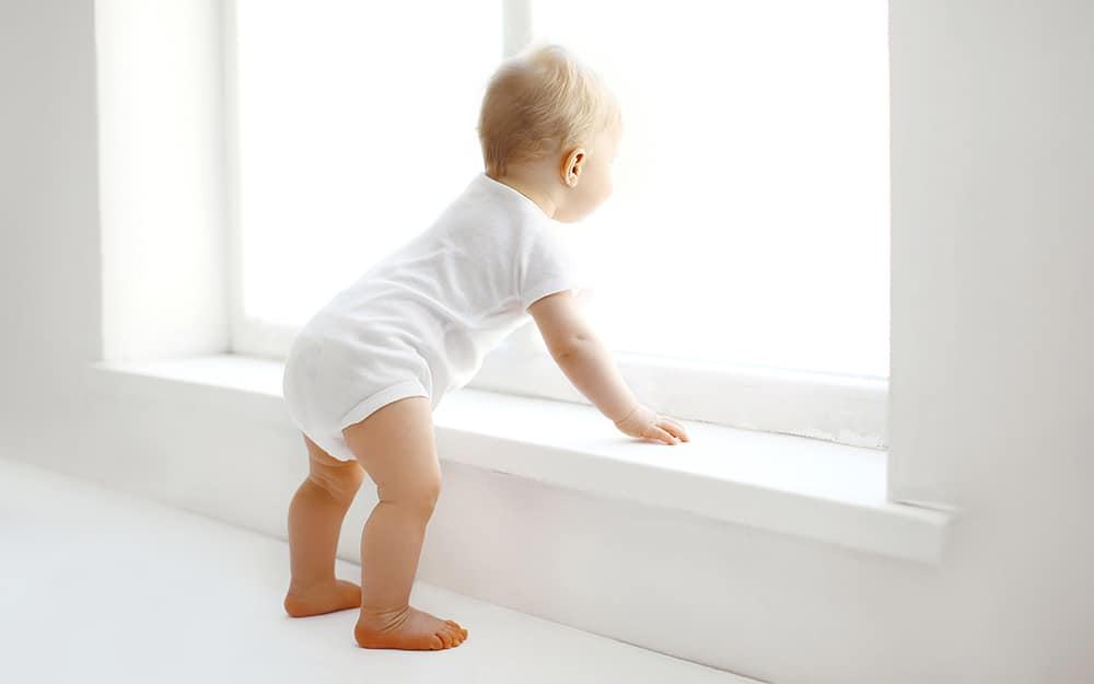 baby leaning on window sill