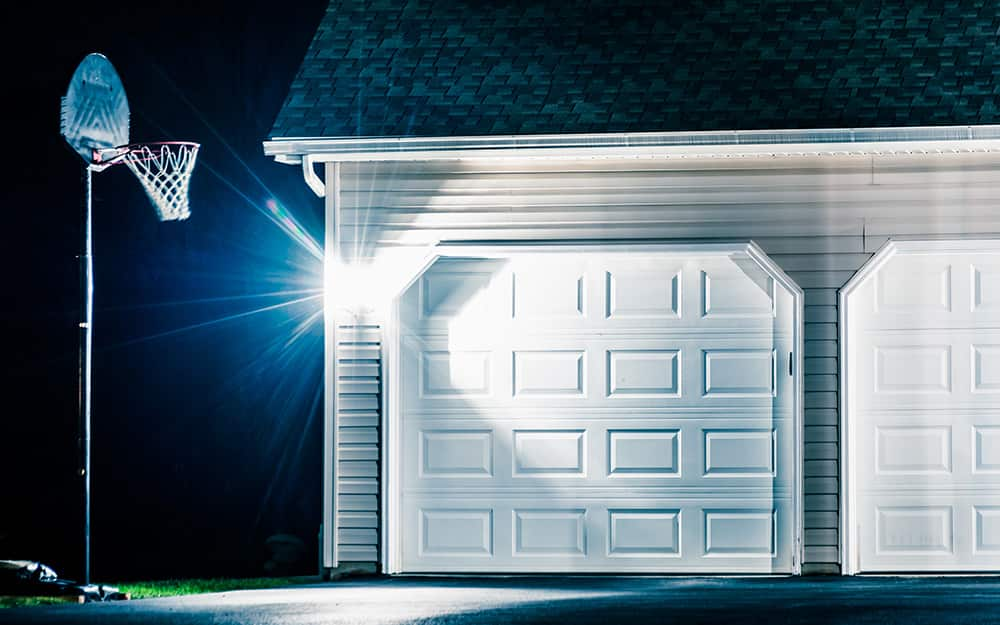 motion lighting in driveway at night with basketball hoop
