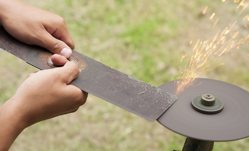 A person sharpening a lawn mower blade.