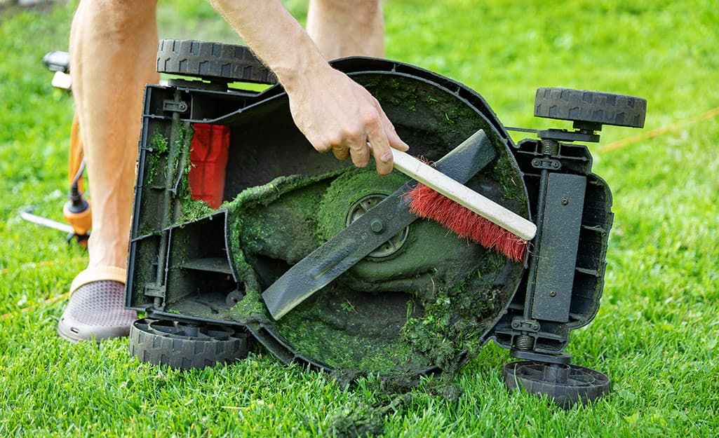A person cleans the bowl around the lawn mower blade.